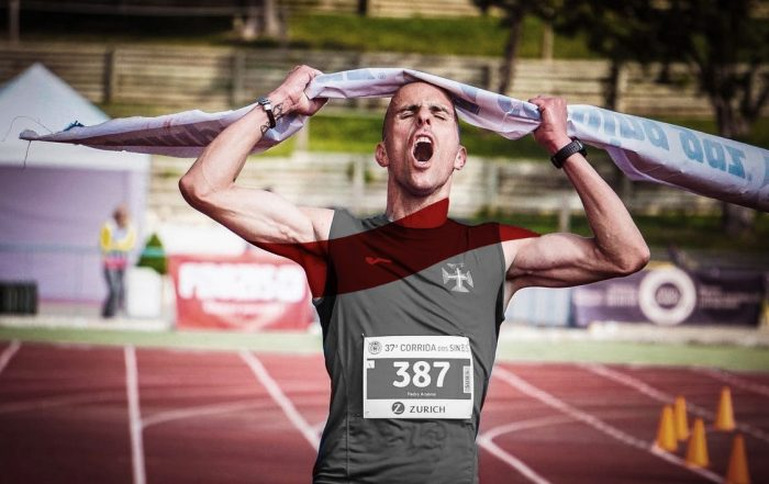 Man wearing gray jersey going through marathon finish line