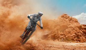 Mountain biker on a desert trail, leaving dust behind him.