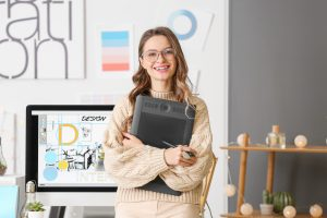 Female office worker smiling while holding a folder.