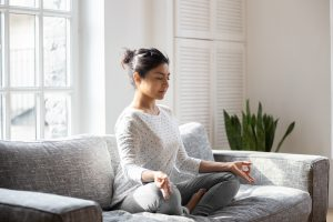 Woman meditating on a couch.