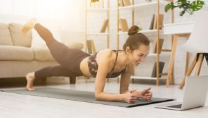Woman is doing a plank while watching a video on her laptop.