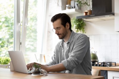 Man typing on his laptop while sitting in the kitchen