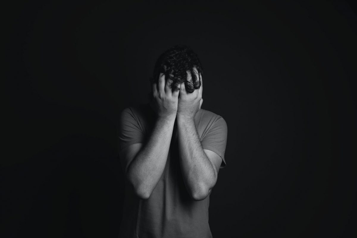 Black and white photo of sad man with his head in his hands.