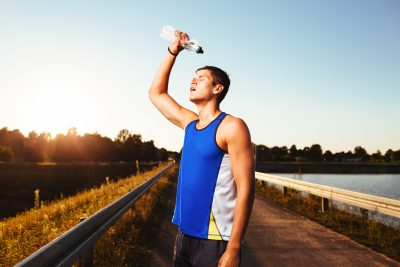 Runner pouring bottled water on his head