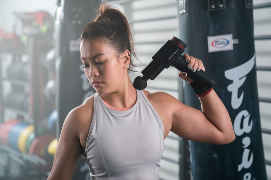 woman using deep tissue massage gun on shoulders