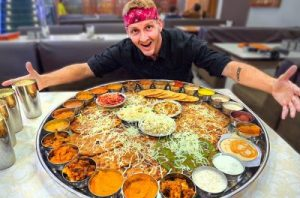 Man wearing bandanna posing with a large platter of food and drinks on a table