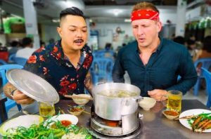 Two men dining together with a boiling pot of soup between them