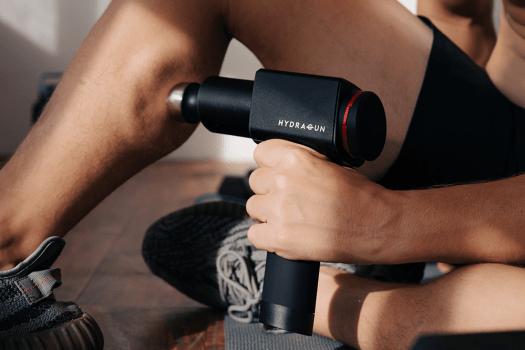 Man using Hydragun deep tissue massage gun on his calves