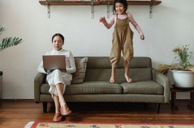 A woman working on the sofa with her laptop, as her daughter jumps on the seat next to her.
