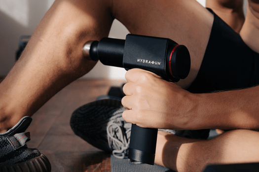 A person uses HYDRAGUN on his calves.