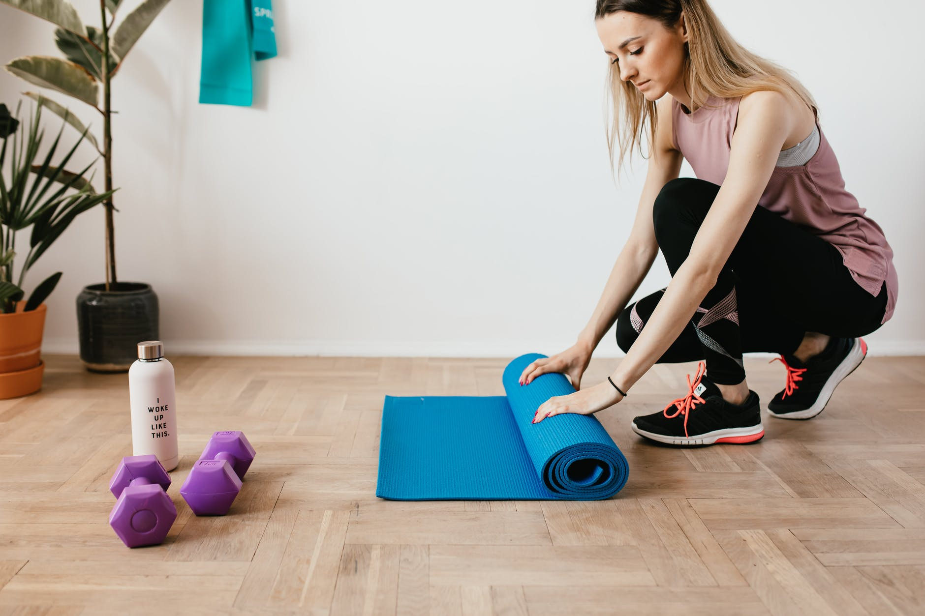 A woman unfolds her workout mat on the floor, a set of weights are seen nearby.