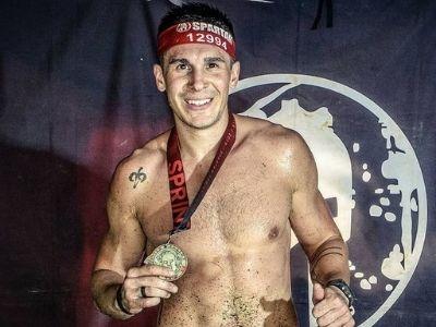 Andrea Cloarec holding a Spartan gold medal.