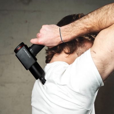 Man using the Hydragun on his shoulder blade