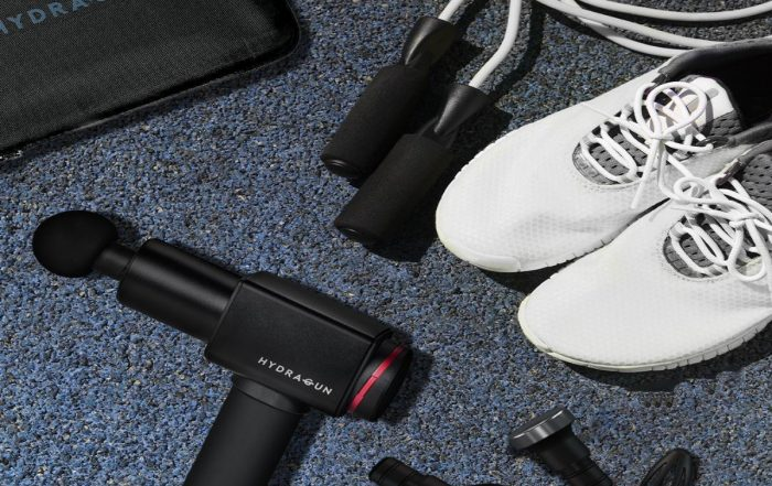 Flat lay of the Hydragun kit, training shoes and jumping rope on the gym floor