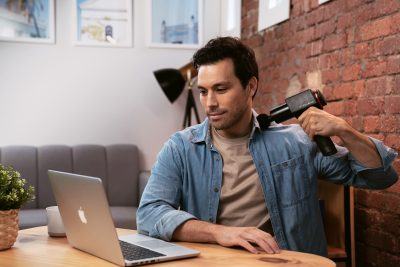 Asian man using a massage gun on his shoulders while sitting on his work desk