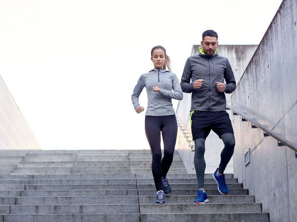 A woman and a woman jogging down the stairs.