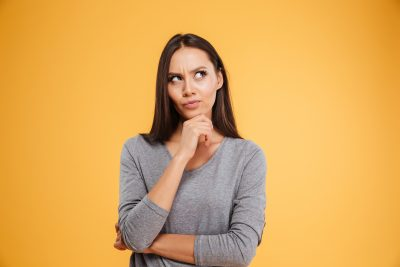 Woman thinking in front of yellow background