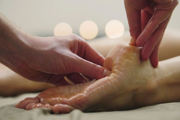 A massage therapist administers a heel massage with a body massage oil.