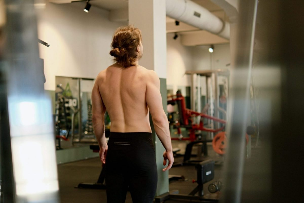 Back view of topless man at a gym