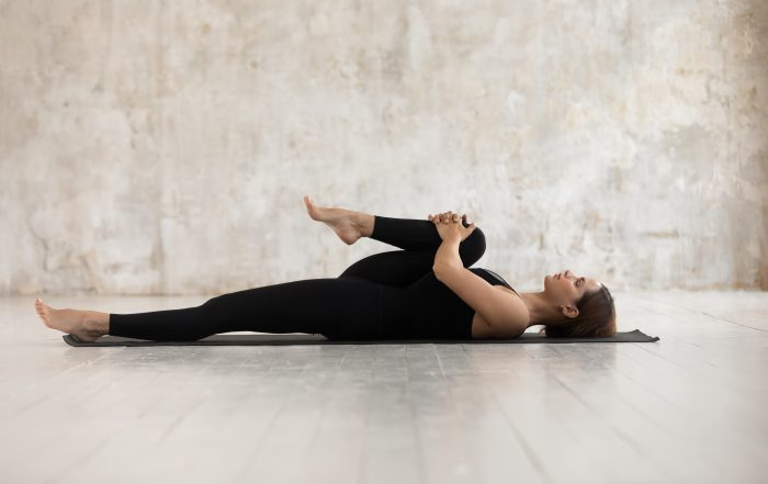 Woman stretching her leg while lying down on yoga mat