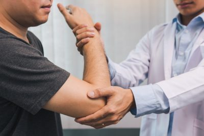 Doctor doing physical therapy on patient's elbow