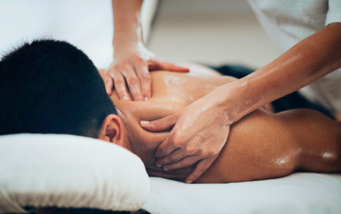 Man lying down getting a sports massage on his back
