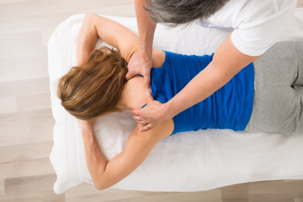 Woman getting a back massage while lying down on a massage bed
