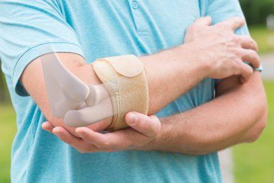 Man holding his braced elbow